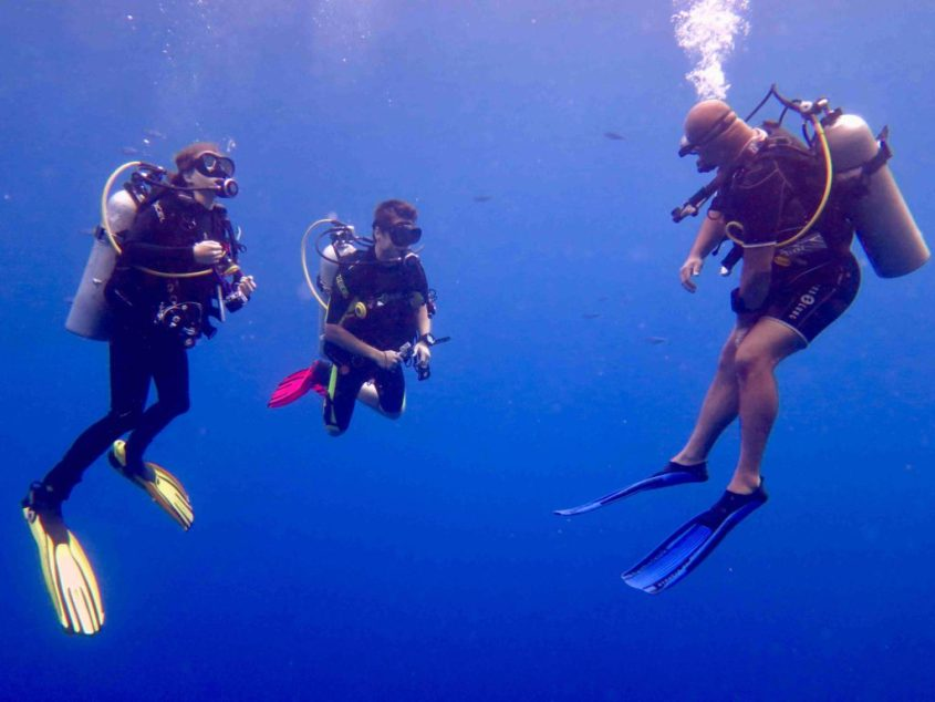 Deux plongeurs sous l'eau regardant leur instructeur