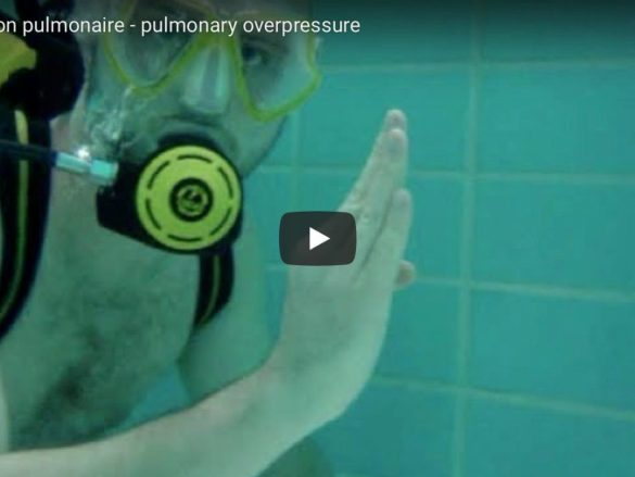 Un plongeur fait le signe ok dans le fond d'une piscine