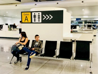 Deux enfants attendent dans le hall d'un aéroport