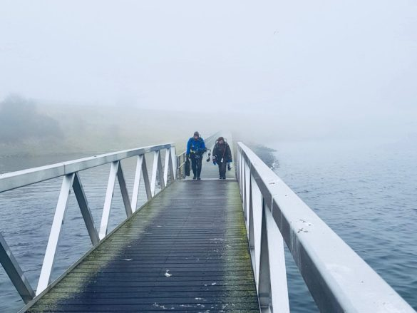 Deux plongeurs marchent sur un ponton.