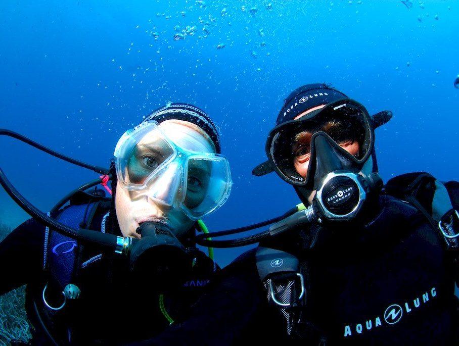 Un plongeur et une plongeuse se prennent en photo sous l'eau lors d'une plongée pour exprimer l'amitié en plongée.