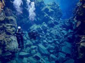 Deux plongeurs devant les éboulements dans la faille de Silfra