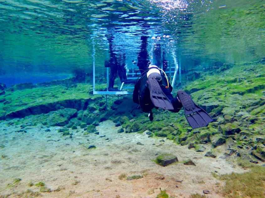 Un plongeur se dirige vers la sortie de l'eau à la faille de Silfra