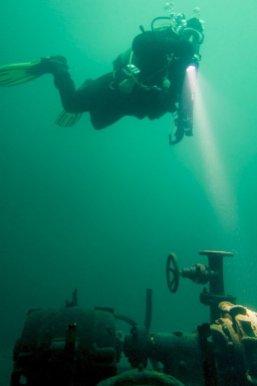 Un plongeur est en apesanteur au dessus de vieilles machines immergées.