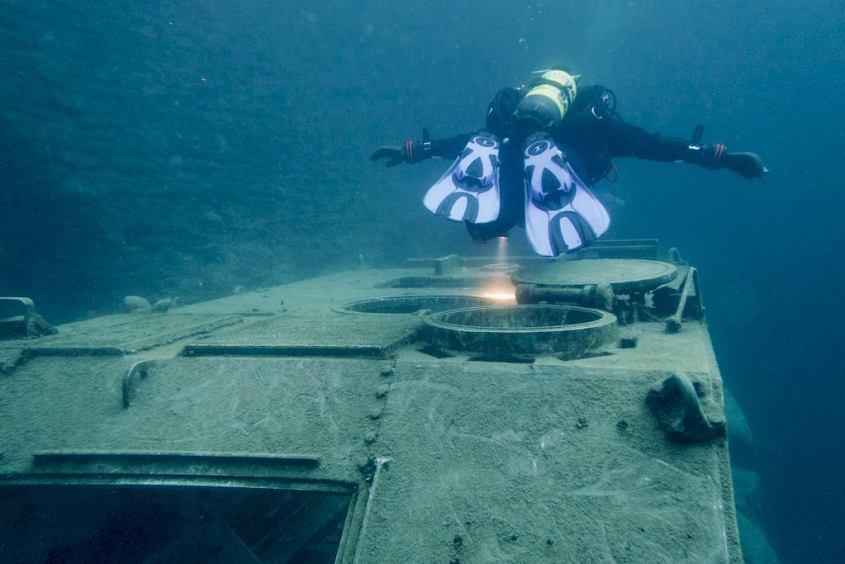 Un plongeur semble survoler le char au fond de l'eau