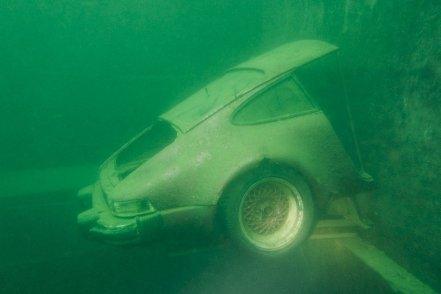Une demi Porsche immergée dans l'eau de la carrière