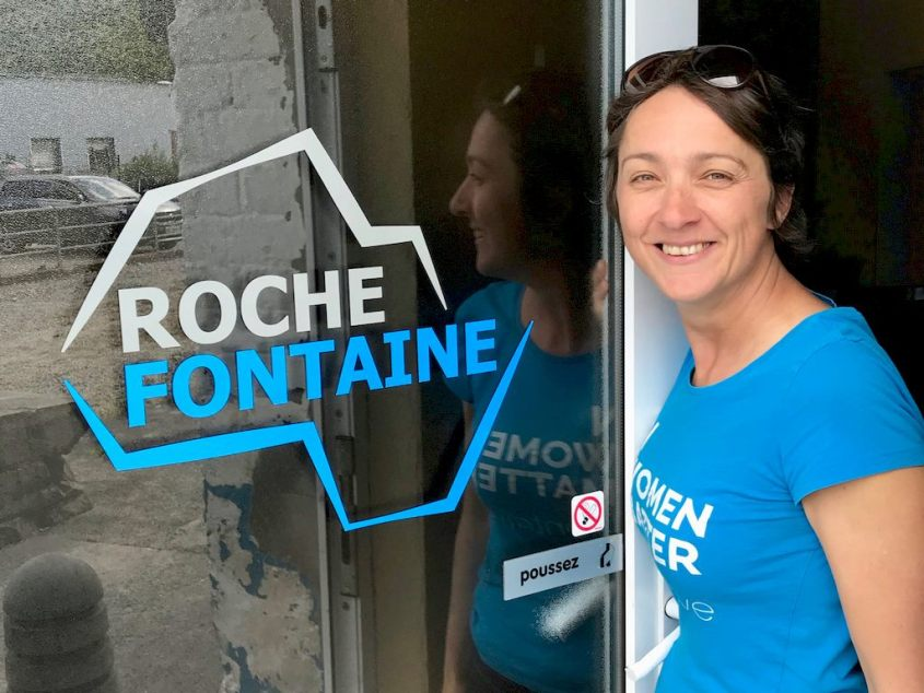 Hélène se tient près de la porte d'entrée qui affiche le nouveau logo de la carrière de Rochefontaine