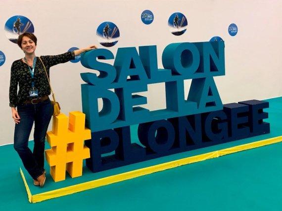 Hélène au Salon de la Plongée 2020 devant l'insigne