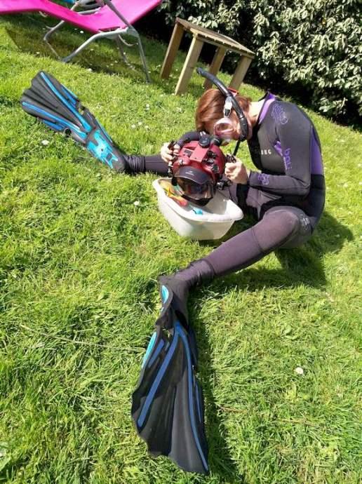 Stéphanie Floirat photographie des jouets dans une bassine assise dans son jardin en équipement de plongée.