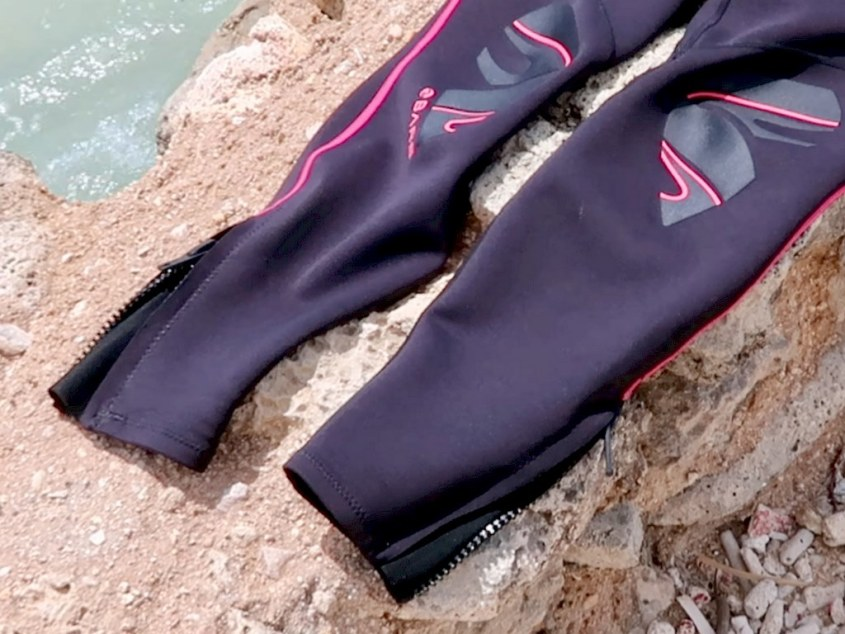 Les jambes de la combinaison NIXIE Ultra de BARE a des tirettes au niveau des chevilles.
