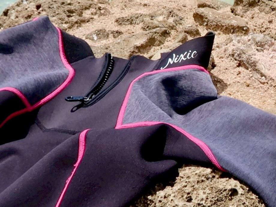 La combinaison NIXIE Ultra de BARE déposée sur une roche en bord de mer.