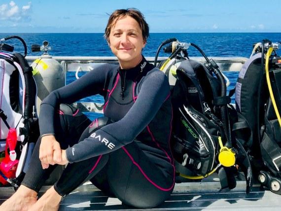 Helène Adam dans sa combinaison NIXIE Ultra de BARE sur un bateau à Bonaire.