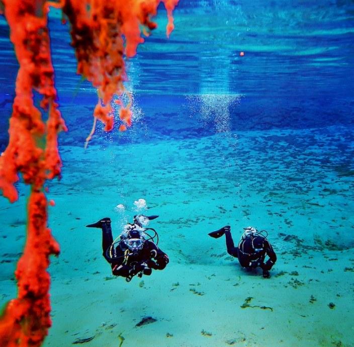 Ces plongeurs évoluant dans la faille de Silfra sont surpris par les nuances de bleu qui sont presque transparent.