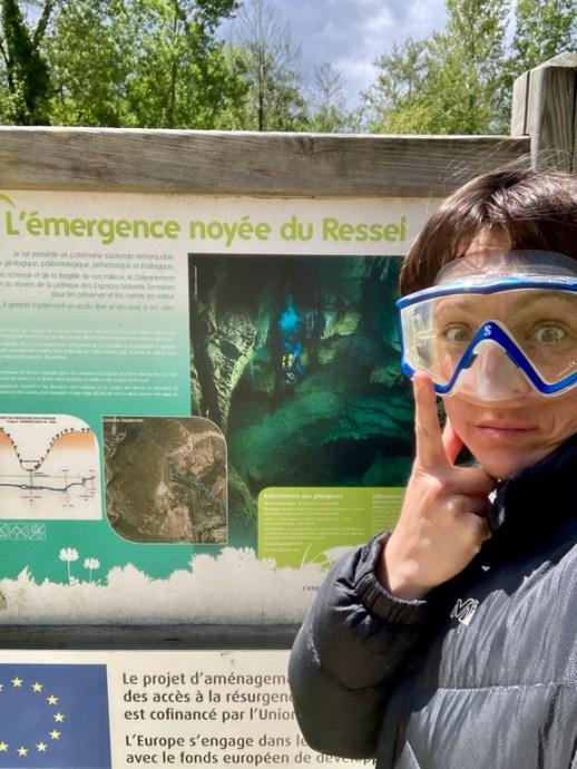 Hélène Adam devant le panneau du site de plongée souterraine du Ressel.