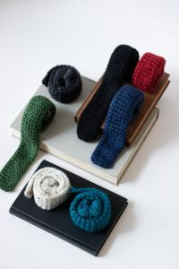 Seven knitted neckties are shown rolled into coils and stacked artfully on some books. Colors shown are teal, tweed, green, charcoal grey, black, navy, red.
