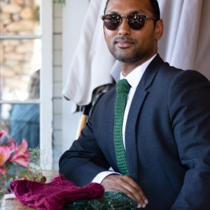 A man look into the camera with a confIdent look on his face. He's wearing a black blazer, white shirt, green knitted necktie and sunglasses.