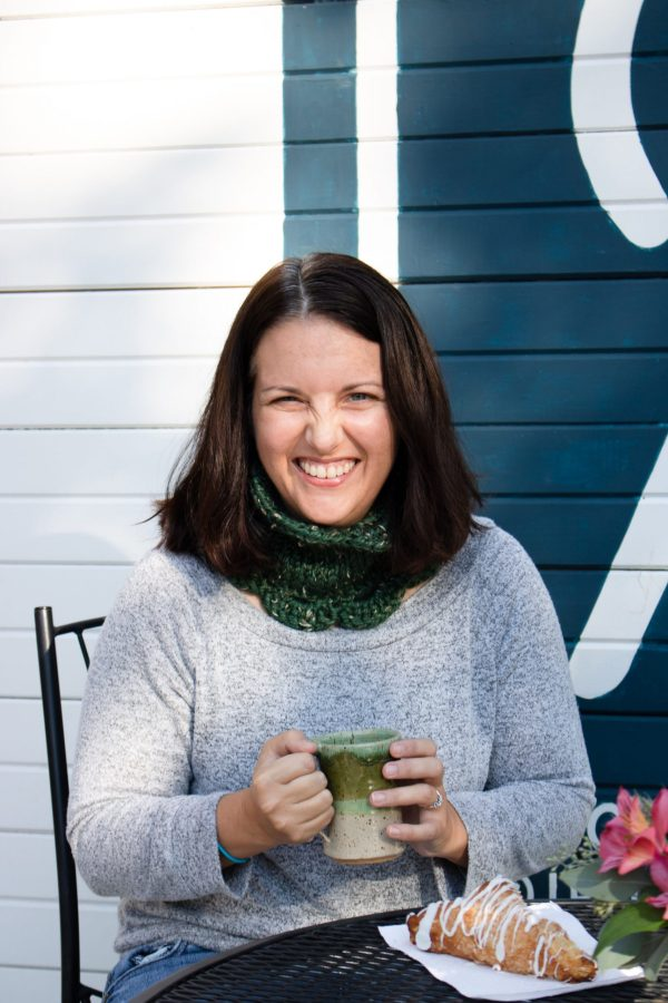 A woman smiles brightly into the camera wearing a grey shirt and a green tweed Marilue Cowl.