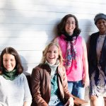 4 women smiling wearing Marilue Cowls. Two women are sitting wearing cowls flipped up. One woman stands with a cowl laced with a scarf. One women stands wearing the cowl as an ear warmer.
