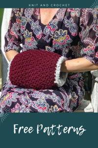 A woman is shown seated in a floral dress. Her hands are tucked into a crocheted hand warmer with faux fur lining. Text at the top says Knit and Crochet. Text at the bottom says Free Patterns.