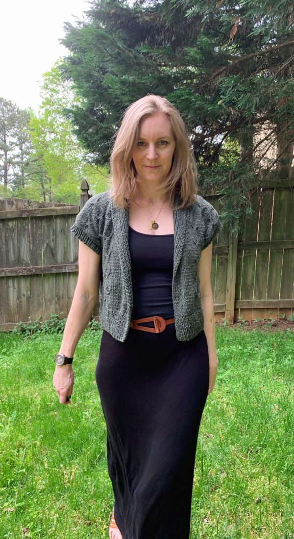 A blond woman wearing a black dress and green knit cardigan is walking toward the camera.