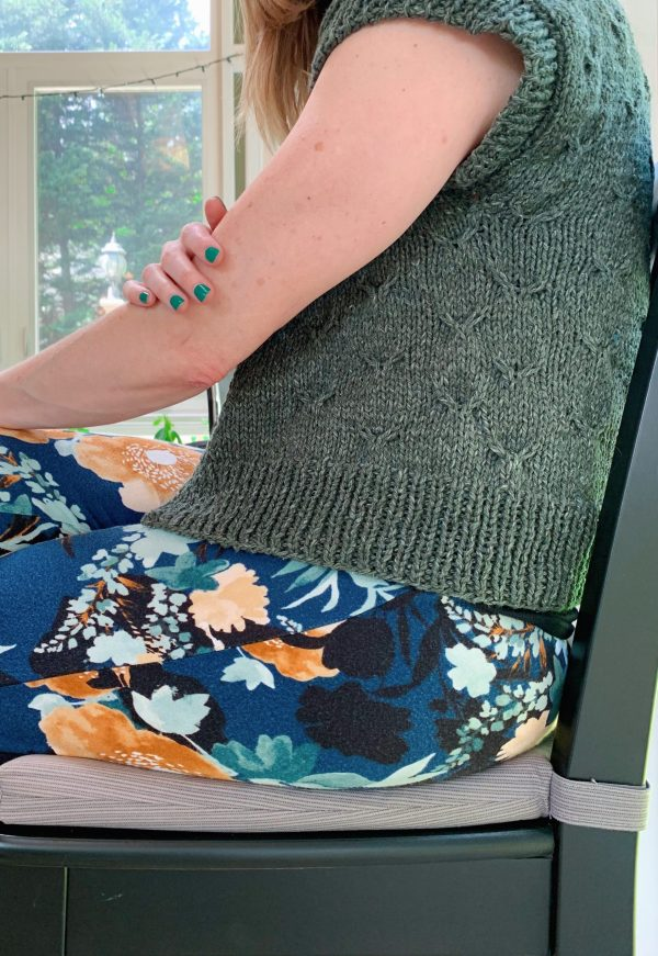 A close up photo of a woman seated wearing pajama pants and a cropped green cardigan.