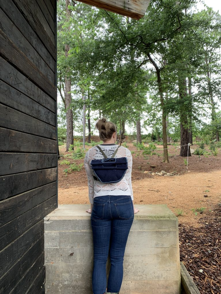 A blonde woman stands with her back to the camera, leaning on a concrete step. She is wearing a white sweater, jeans, and has a blue crocheted backpack with olive green straps