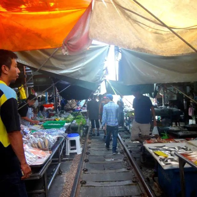 Maeklong Railway Market is a market with a train running through it close ot Bangkok. Here's how to get to Maeklong Railway Market on a day trip.