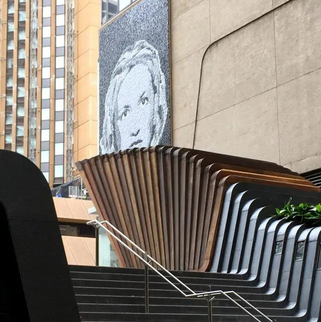 The face on this mural on Sydney's George Street is made from the bottom of glass jars - which is why it's one of quirky things to see in Circular Quay.
