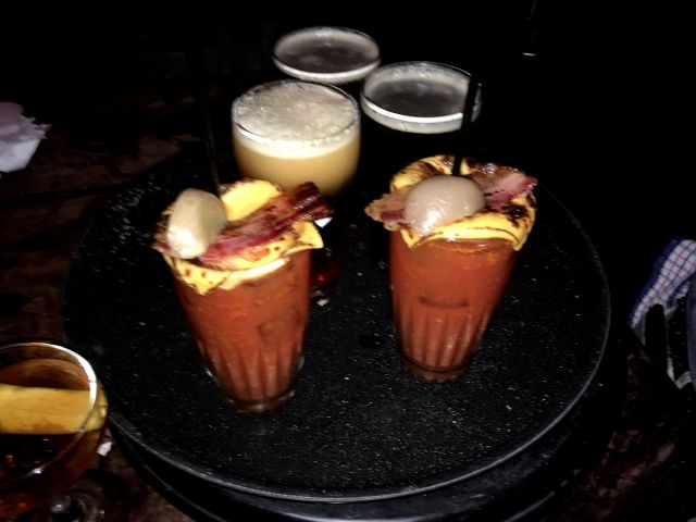 Red coloured drinks with melted cheese and bacon top