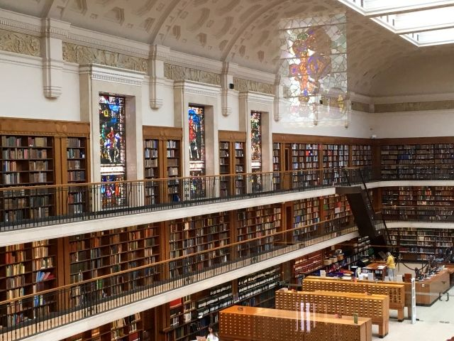 room with stained glass windows, lined with bookshelves filled with books