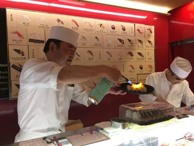 Chef blow torches sushi at the Cyoh standing sushi bar near Tsukiji market Tokyo