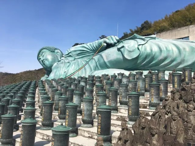 Image of the Buddha at Nanzoin Temple, Fukuoka showing the coloured ropes in his hand. Holding these while praying is said to impart Buddha's wisdom.