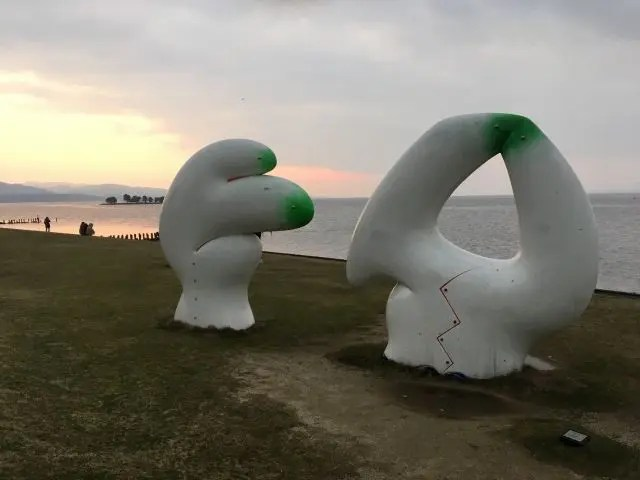 A modern sculpture of a white hand and a white shape on the shore of Lake Shinji in Matsue Japan with the sun setting behind it
