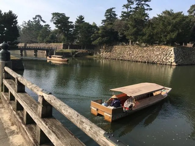 Small boats with drivers in conical hats on Matsue Castle moat, Japan