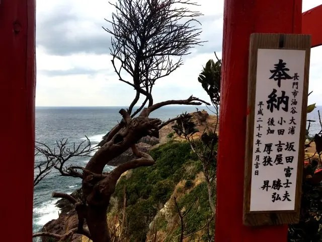 The view looking between the scarlet torii gates of Motonosumi Inari shrine is of trees, rocks and waves.