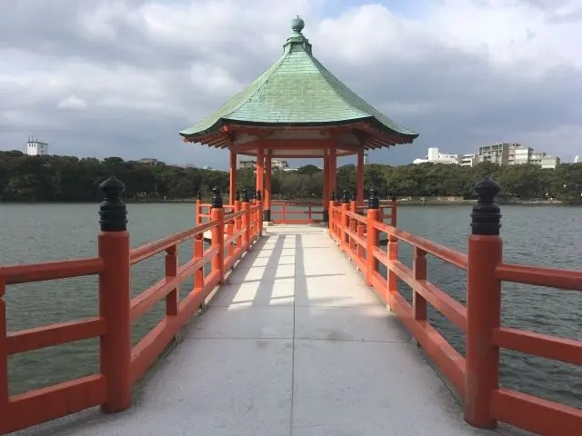 Pagoda in Ohiri Park. It's set in a lake and has bright red railings and a green pagoda style roof.