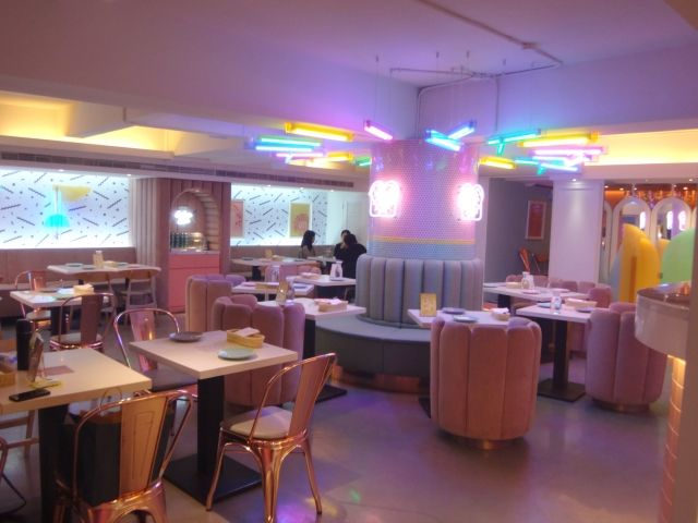 Interior of Bad Ass Babes cafe in Taipei. It has pink and blue sofa seats and gold chairs. The walls and ceiling have neon pastel lights.