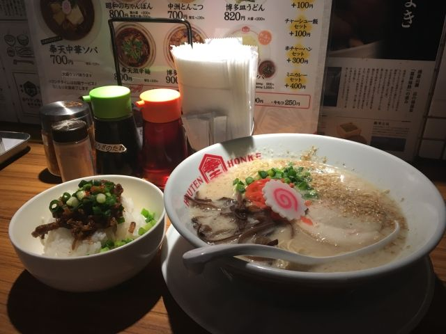 Bowl of Tonkatsu ramen. This has a milky white broth and is topped with green seaweed, spring onion and pork slices.