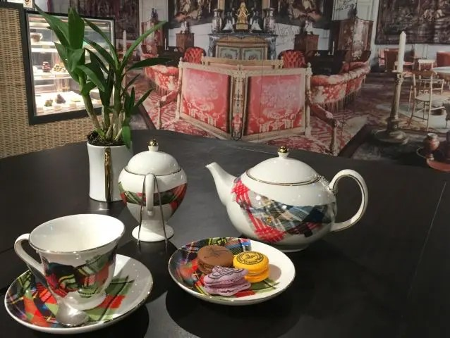 Tea service at the Vivienne Westwood Cafe Taipei. There's a cup, sugar pot and teapot covered in tartan and her signature orb. Then three macarons - brown, purple and yellow - all stamped with her orb.