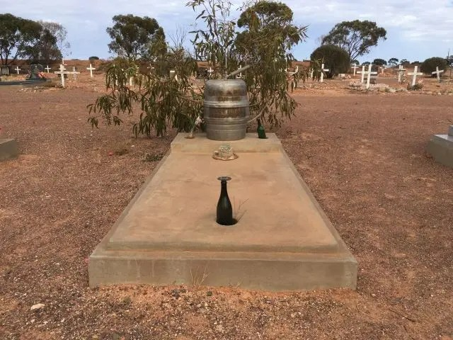Grave of Karl Bratz, Coober Pedy Cemetery. It has a large stone top with a hole in. A beer bottle is balanced in this. On the top is a beer keg marked 'have a drink on me'.