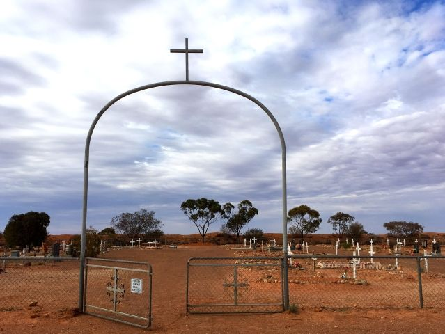 Simple iron arch with a cross on top marks the entry to BootHill Cemetery in Coober Pedy