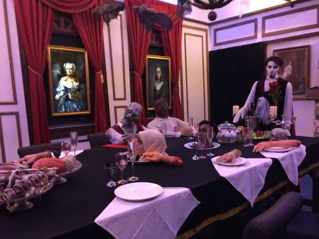 Table scene at the Ghost Museum - man has his head through the table pretending to be served for dinner