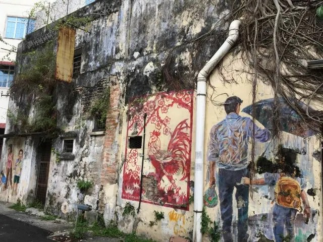 murals paited on a wall in Ipoh Malaysia with tree roots growing through them