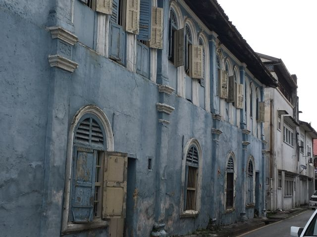 old buildings with peeling blue pant and white shutters Ipoh