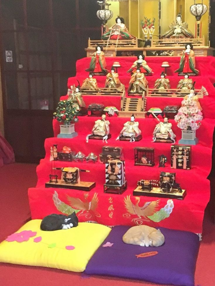 Red staircase full of Hina dolls with two cat dolls at the bottom