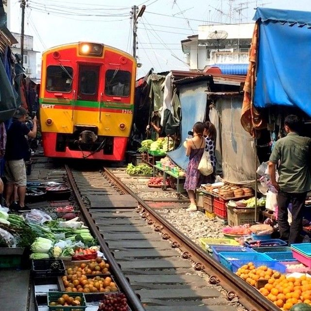Train going down a railway track surrounded by fruit and vegetables at Maeklong Railway Market near Bangkok, Thailand