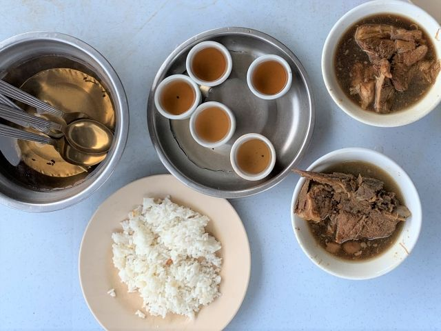 Bowls of Bak Kuh Tek, rice and tea soaking cutlery in Klang, Malaysia