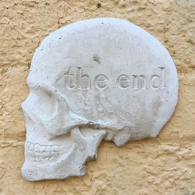 Skull with The End written on it, stuck to wall - by artist Will Coles in Sydney
