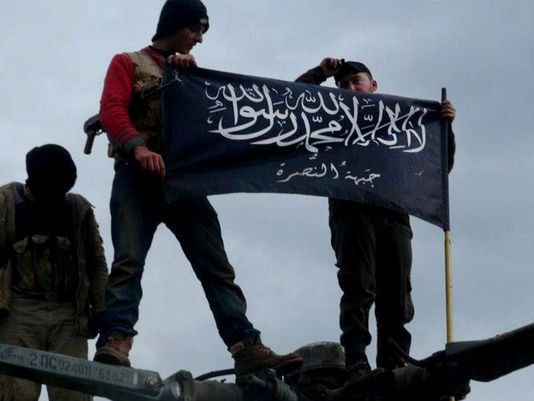 Syrian rebels waving an Al Qaeda flag over a government helicopter at a captured airbase.