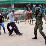 Police officer teargases a UPND cadre in Lusaka